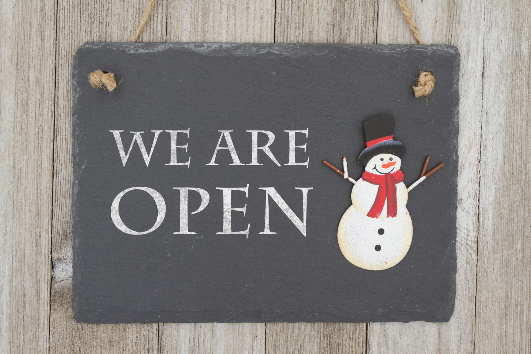 Old fashion Christmas store message, A retro chalkboard with a snowman hanging on weathered wood background with text We are Open